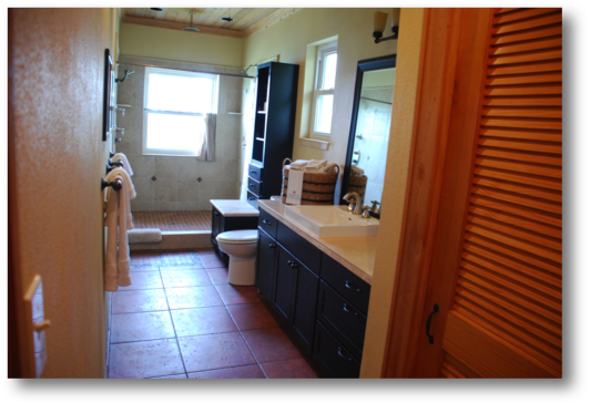 Master bathroom includes three shower heads, bath linens all overlooking the ocean
